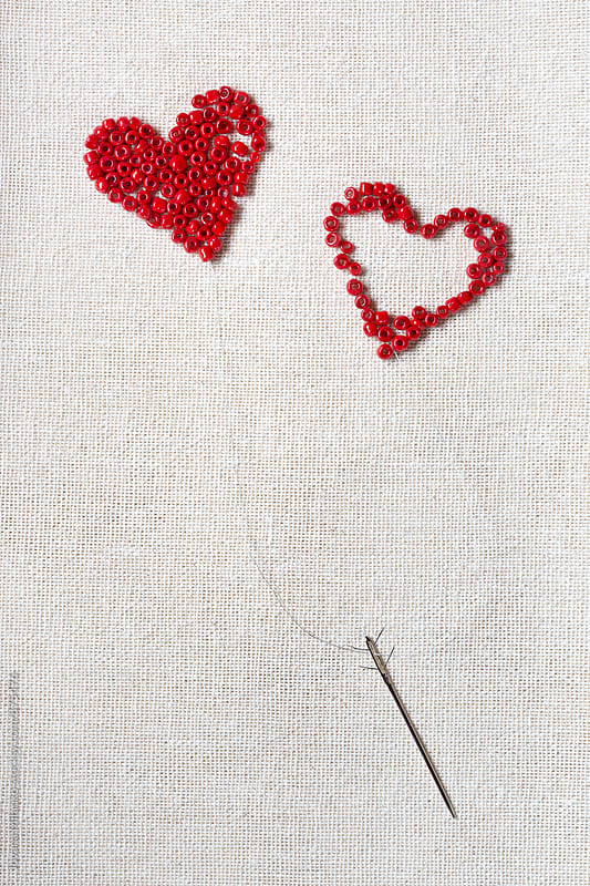 Red beads in heart shape connected with arrow like needle  by Jovana Milanko for Stocksy United