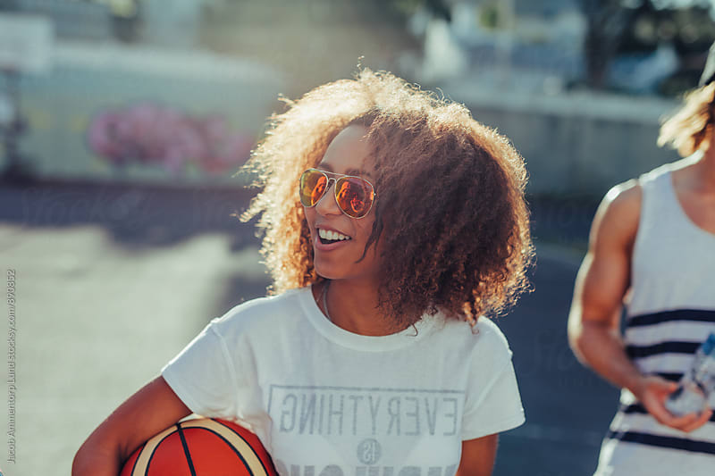 Happy young african woman with a basketball  by Jacob Ammentorp Lund for Stocksy United