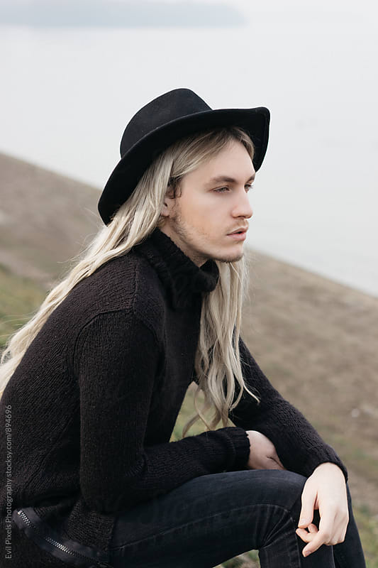 Portrait of a male model with long hair and black hat sitting near river by Evil Pixels Photography for Stocksy United