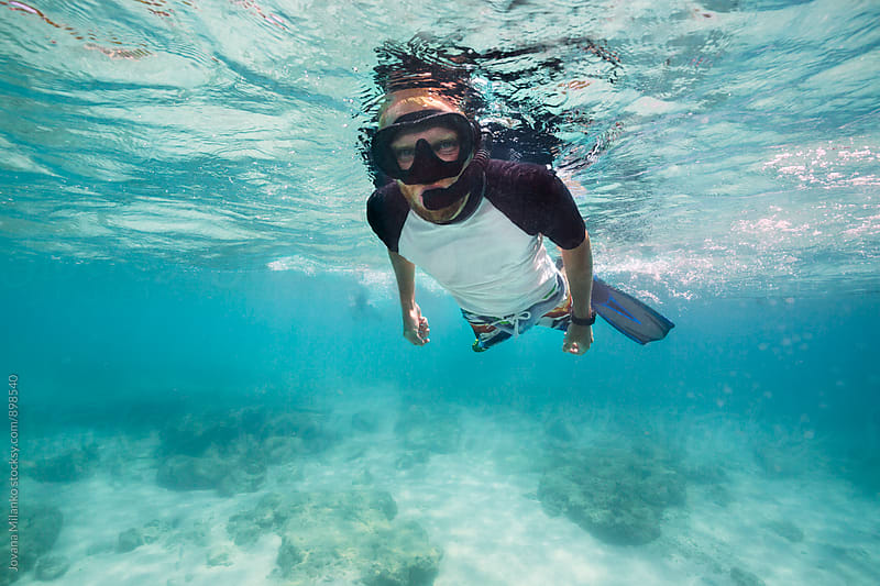 Young blond man snorkeling in tropical waters  by Jovana Milanko for Stocksy United