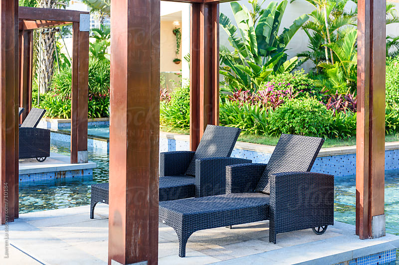 Wmpty chairs for relaxation in garden of resort by Lawren Lu for Stocksy United