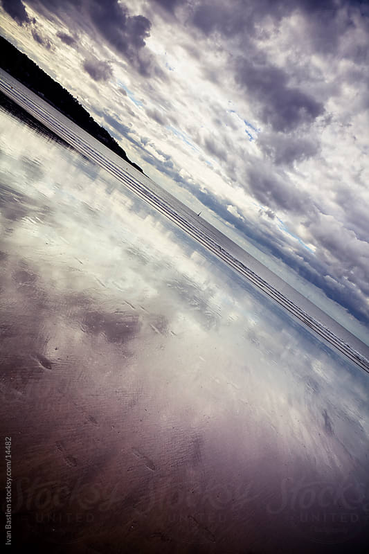 Reflection of the cloudy sky in a beach at low tide by Ivan Bastien for Stocksy United