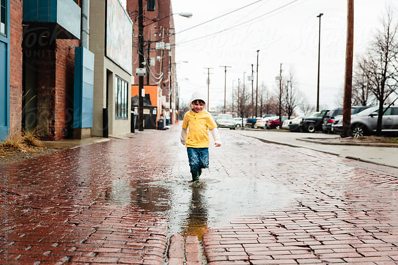 Young boy runs through large puddle on rainy day by Maria Manco for Stocksy United