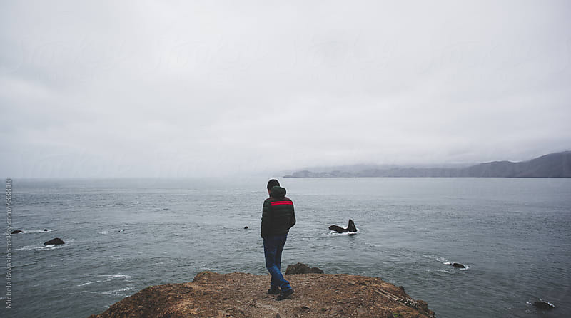 Man looking at the ocean, San Francisco coast by michela ravasio for Stocksy United