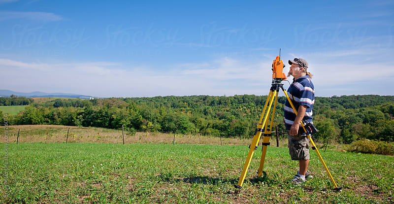 Land Surveyor Instrument Operator Working in Field by Brian McEntire for Stocksy United