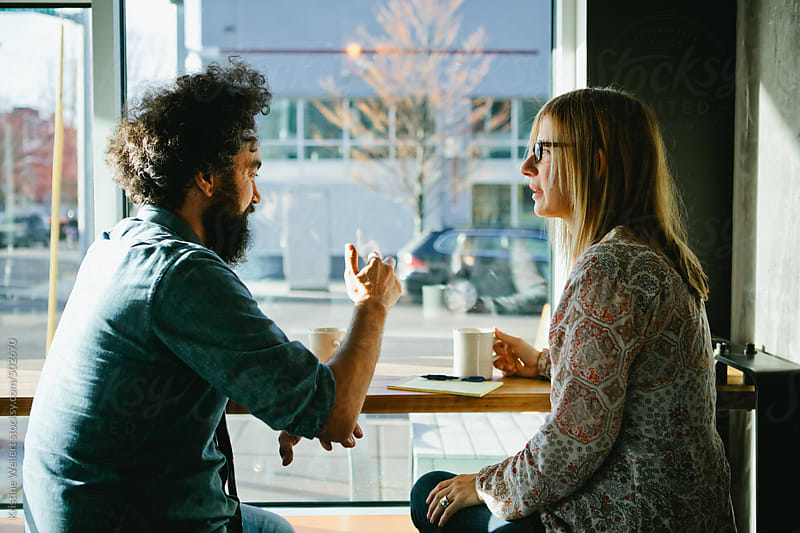 Man and Woman having a discussion over coffee by Kristine Weilert for Stocksy United
