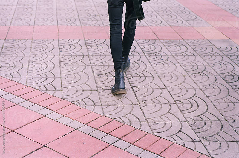 Legs of a person walking across a light pink tiled floor by Jovo Jovanovic for Stocksy United