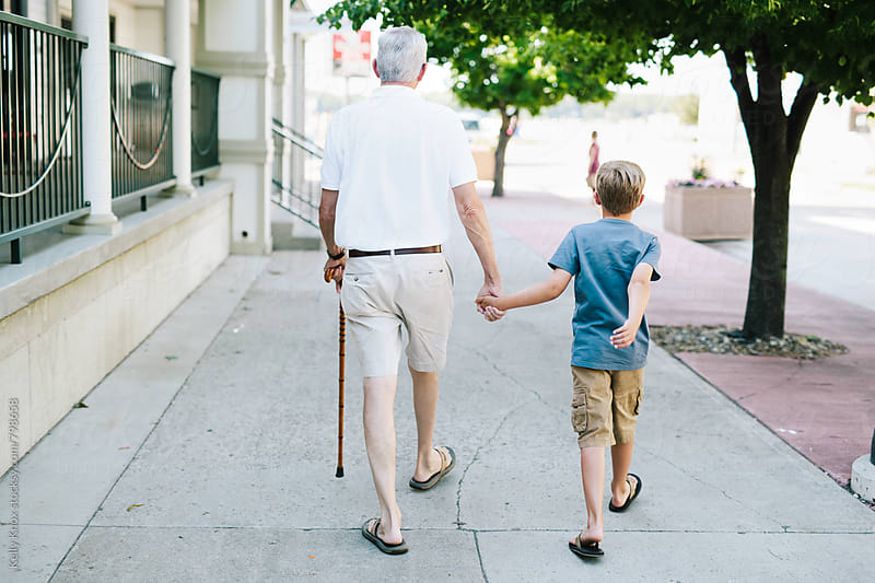 grandfather and grandson walking hand in hand  by Kelly Knox for Stocksy United