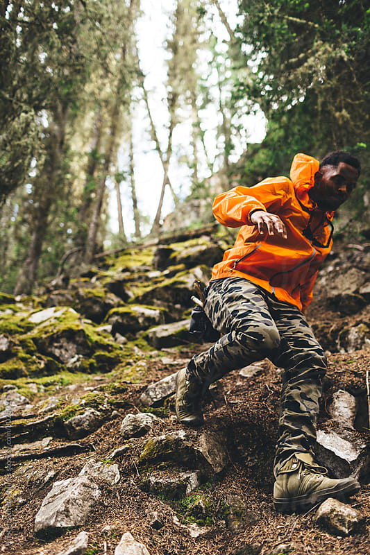 A man climbing down a rocking hill wearing a orange wind jacket by Kristen Curette Hines for Stocksy United