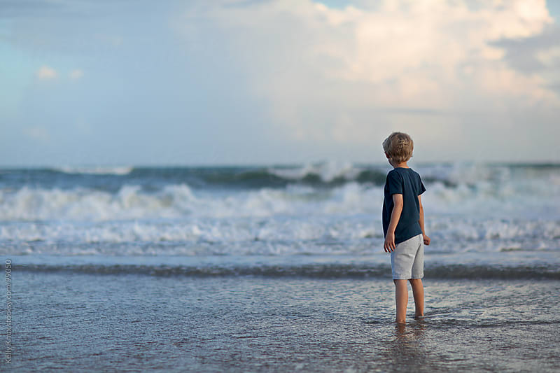 boy wading in the ocean by Kelly Knox for Stocksy United