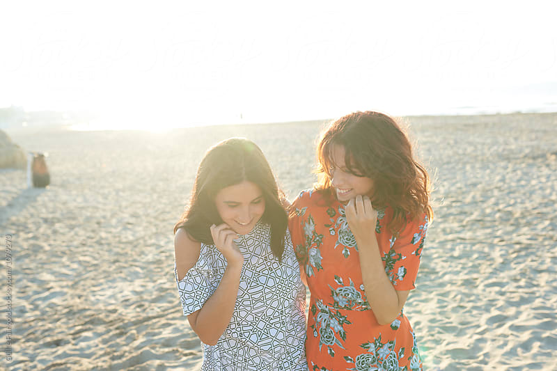 Two smiling happy girlfriends walking on beach in sunrise by Guille Faingold for Stocksy United