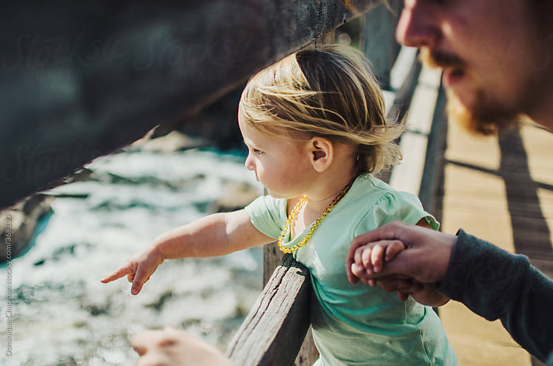 Small child pointing at river with father by Dominique Chapman for Stocksy United