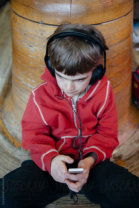 Child wears headphones while listening to music on an mp3 player by Cara Dolan for Stocksy United