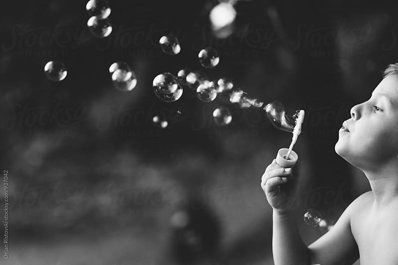 Boy blowing bubbles. by Dejan Ristovski for Stocksy United