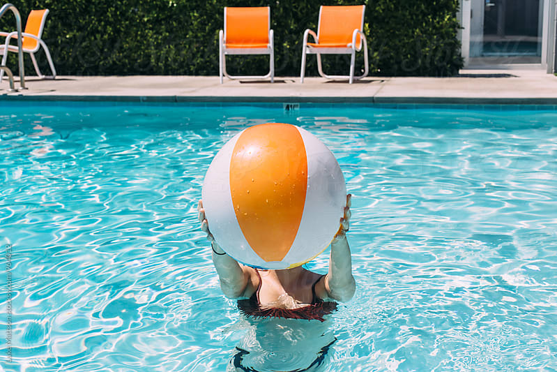 Young Woman In Swimming Pool Holding Beach Ball In Front Of Face by Luke Mattson for Stocksy United