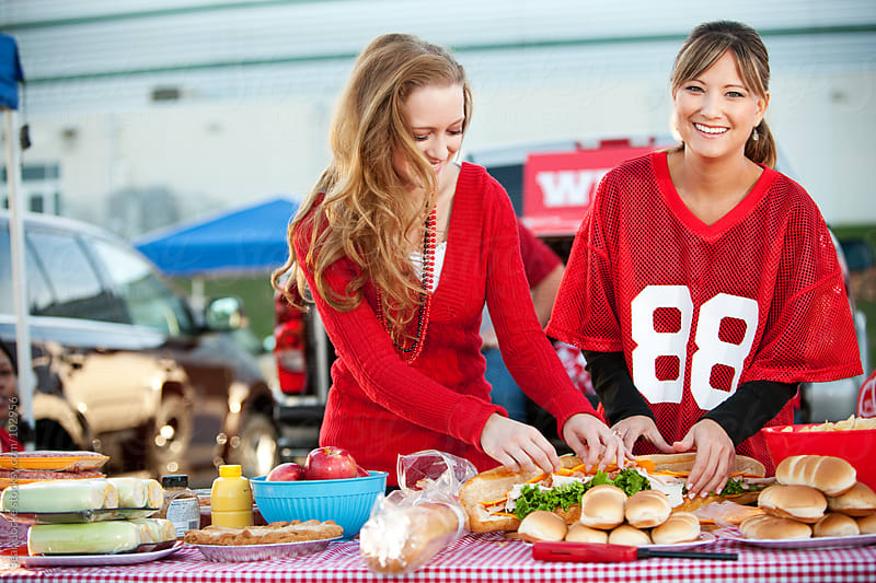 Tailgating: Laughing Woman at Food Table by Sean Locke for Stocksy United
