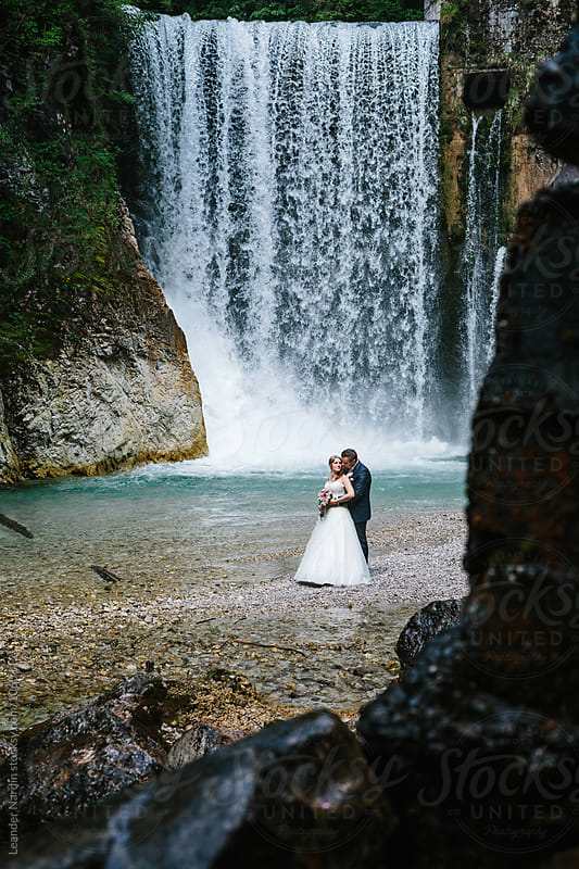 loving bridal couple in front of a big waterfall on a rocky beach by Leander Nardin for Stocksy United
