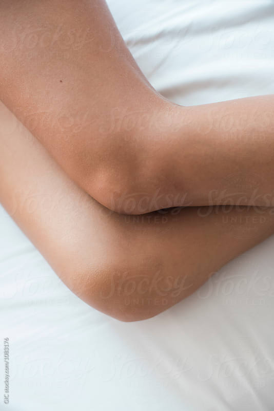 Legs close up on the bed by Simone Becchetti for Stocksy United