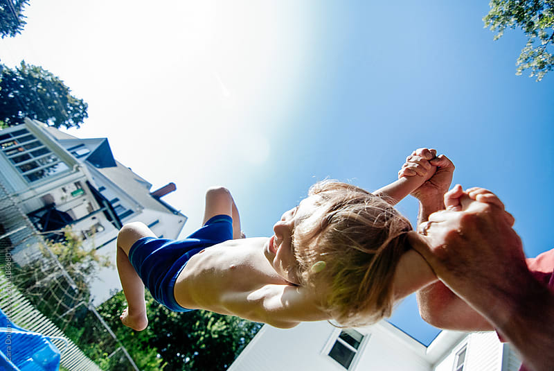 Happy toddler boy swings, hanging onto his dad's hands by Cara Dolan for Stocksy United