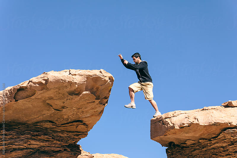 Young man jumping from rock ledge to another rock by Alejandro Moreno de Carlos for Stocksy United