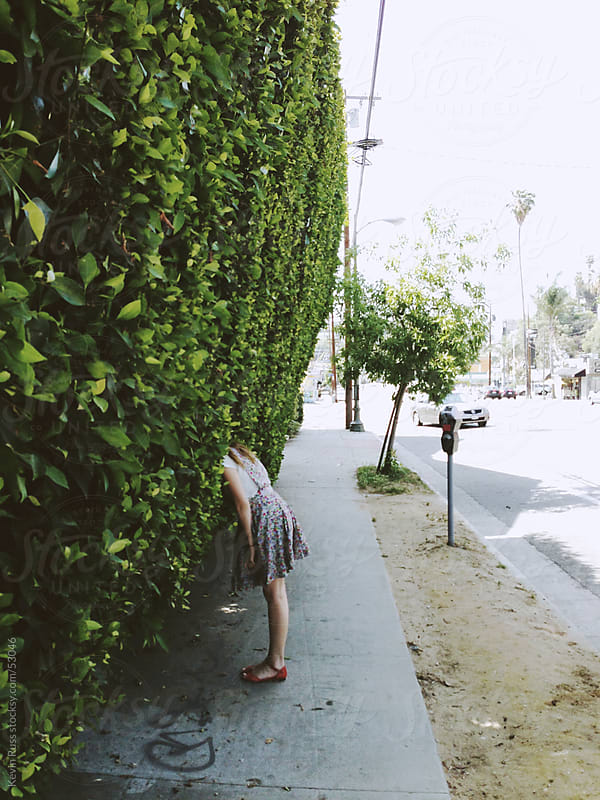 Woman Sticking Her Head in a Hedge by Kevin Russ for Stocksy United