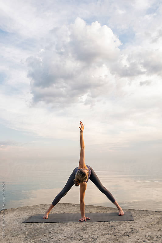 Unrecognizable girl practicing yoga against of white clouds over sea by Danil Nevsky for Stocksy United