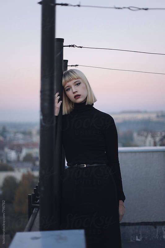 Beautiful stylish woman looking at camera standing on the roof of the building during sunset by Marija Mandic for Stocksy United