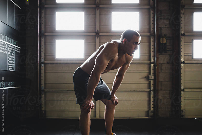 Portrait of young, fit and sweaty man recovering in gritty gym by Rob and Julia Campbell for Stocksy United