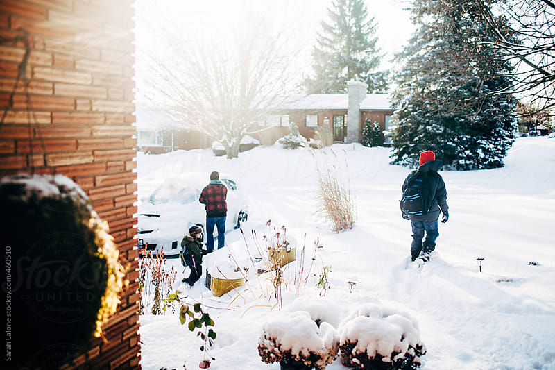 boys and their father on a snowy day by Sarah Lalone for Stocksy United