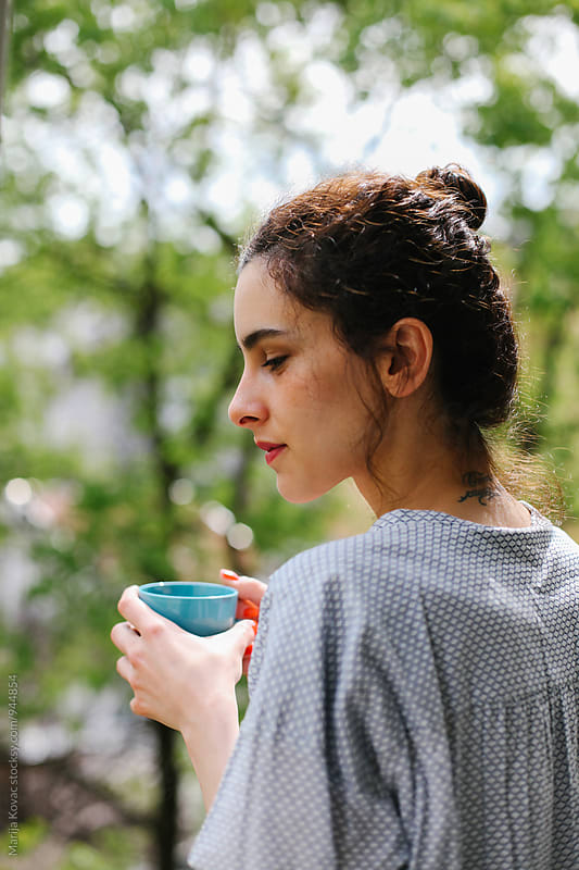 Beautiful young woman holding a cup of a coffee by Marija Kovac for Stocksy United