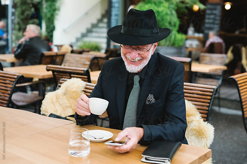 Elegant senior businessman using a phone sitting at cafe by GIC for Stocksy United