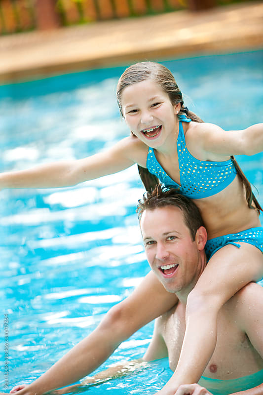 Swimming: Girl Riding Piggyback with Father by Sean Locke for Stocksy United