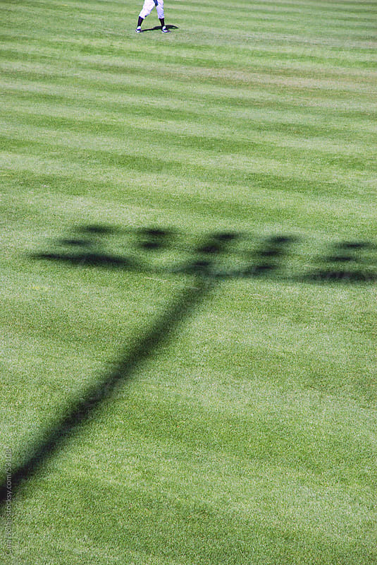 Shadow of baseball stadium lights on field with outfielder by Cara Dolan for Stocksy United