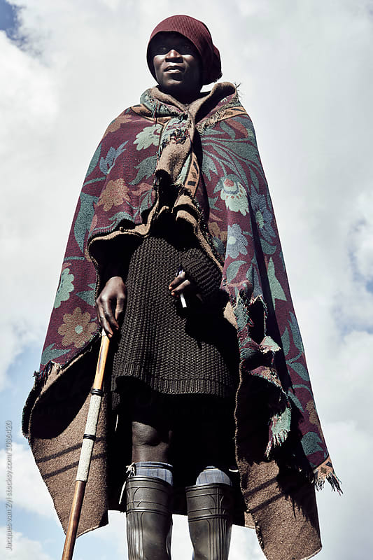 A portrait of a black Basotho shepherd against a clouded sky. by Jacques van Zyl for Stocksy United