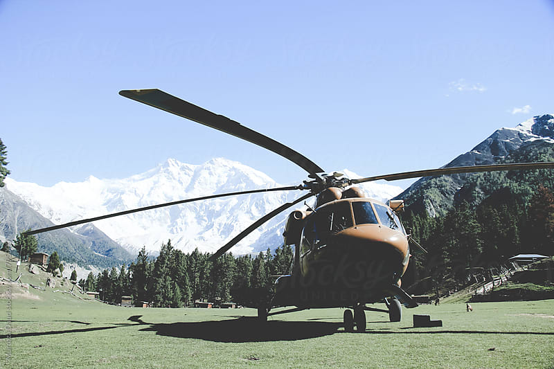 A helicopter parked in pasture between mountains by Murtaza Daud for Stocksy United