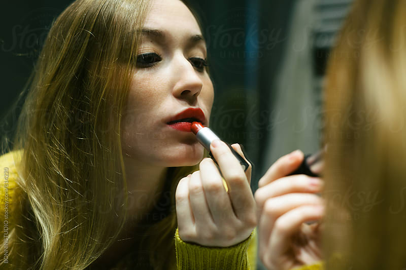 Beautiful woman applying red lipstick in front of a mirror. by BONNINSTUDIO for Stocksy United