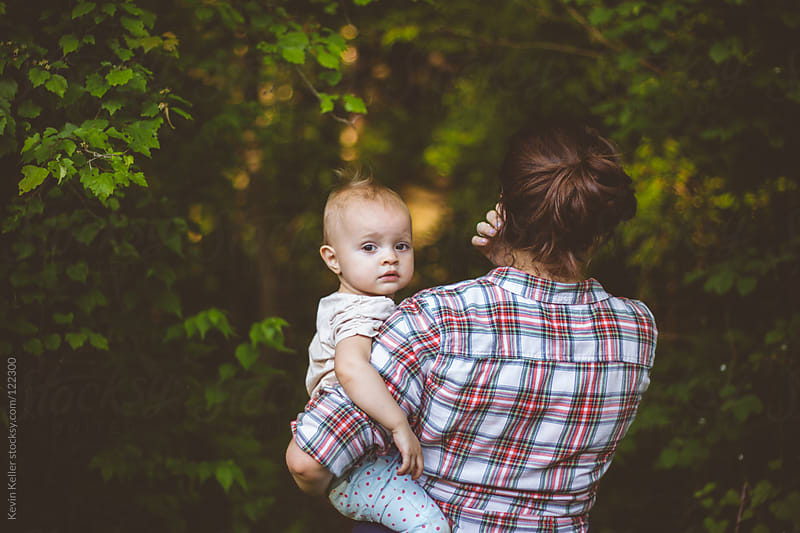 Toddler Girl Looking Back in the Arms of Her Mother by Kevin Keller for Stocksy United