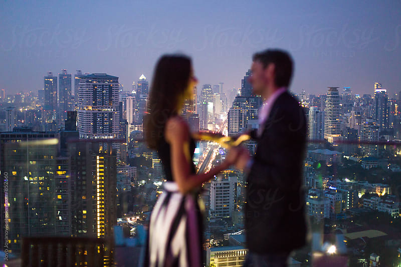 Silhouettes of a stylish and elegant young couple holding hands in a rooftop bar at night  by Jovo Jovanovic for Stocksy United