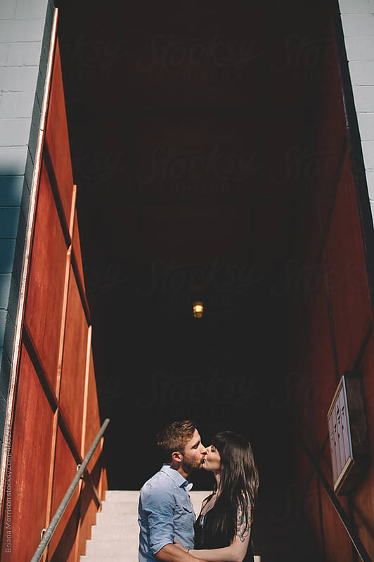 Cute Young Couple Kissing in Outdoor Hallway by Briana Morrison for Stocksy United