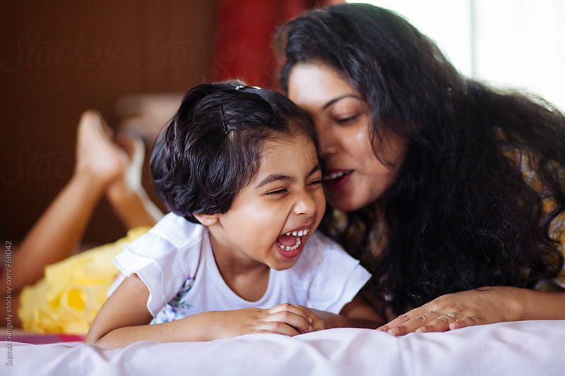 Mother whispering into her daughters ear,happy family by Saptak Ganguly for Stocksy United