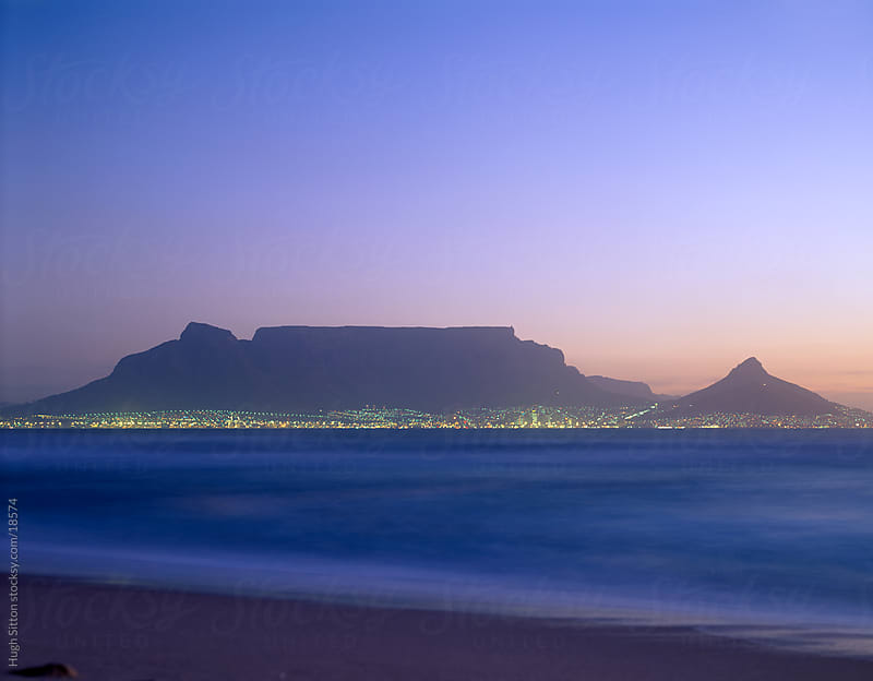 Table Top mountain, with the lights of Cape Town below at dusk. South Africa. by Hugh Sitton for Stocksy United