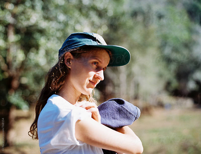 Young girl in cap by Dina Lun for Stocksy United