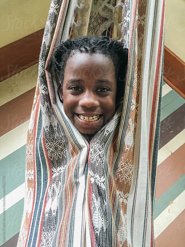 Smiling black girl in a hammoc by Gabriel (Gabi) Bucataru for Stocksy United