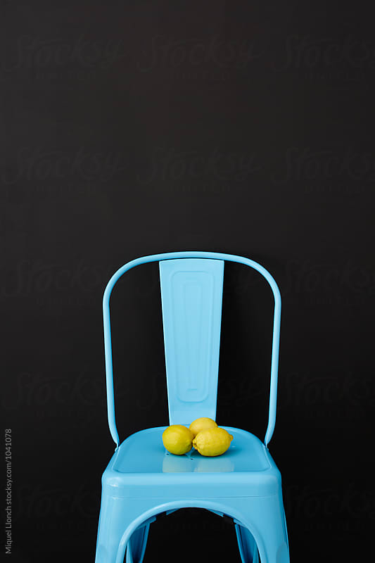 Blue metallic chair whith black background and fresh lemons by Miquel Llonch for Stocksy United
