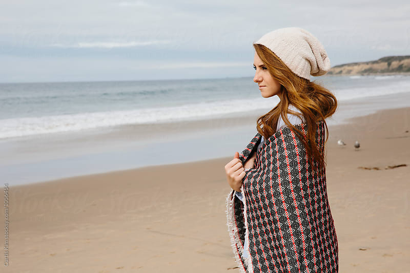 Young woman at the beach with blanket over her shoulders by Curtis Kim for Stocksy United