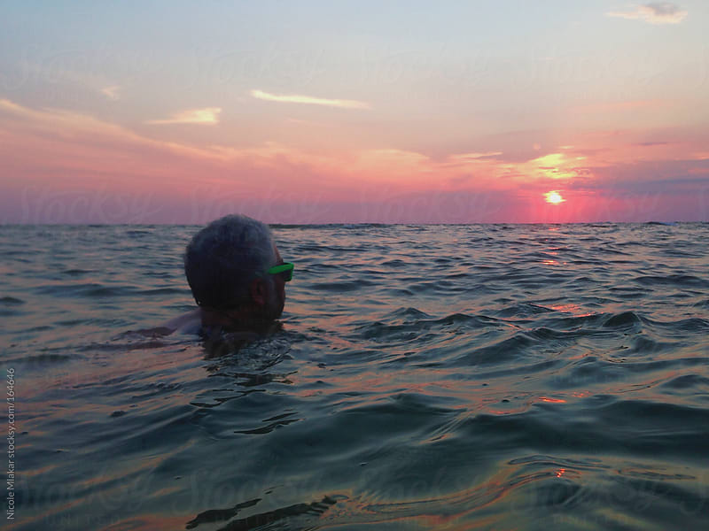 Man swimming in the ocean at sunset with sunglasses on.  by Nicole Mlakar for Stocksy United
