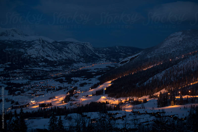 Skiing center with lights by night with snow covered mountains. by Jonas Räfling for Stocksy United