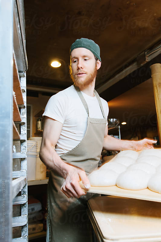 Baker loading storage racks with raw shaped bread dough at a commercial artisinal bakery by Mihael Blikshteyn for Stocksy United