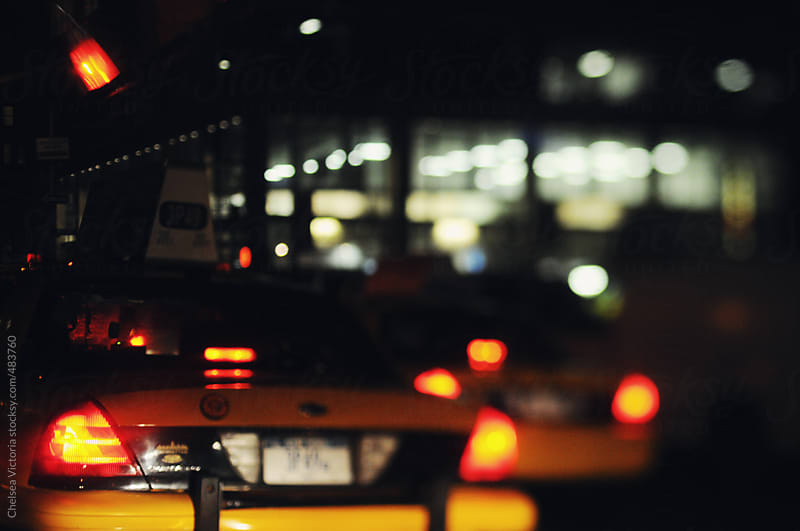 Taxis drive at night in Manhattan by Chelsea Victoria for Stocksy United