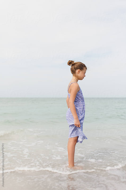 Profile of preteen girl standing in the ocean looking out at the water by Amanda Worrall for Stocksy United